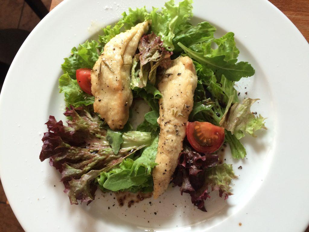 Eine halbe Portion Hähnchenbrust mit Rosmarin auf Salat